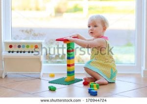 stock-photo-adorable-toddler-girl-playing-with-plastic-blocks-sitting-on-the-tiles-floor-next-to-a-big-window-170944724