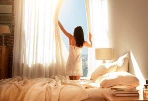 getty_rm_photo_of_woman_opening_curtains_in_morning